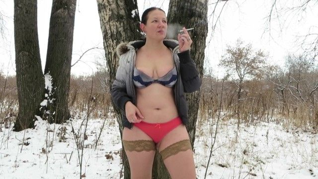 Smokes in the winter forest milf in nylons and red pants